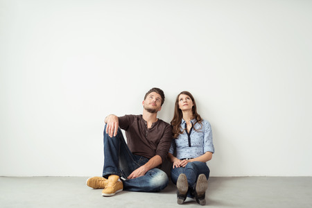 parejas: Pensativo joven pareja sentada en el suelo y mirando hacia arriba contra la pared vacía del fondo blanco con copia espacio.