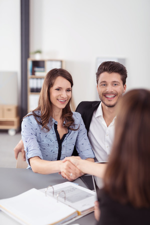 advice: Happy Sweet Young Couple Handshaking a Real Estate Agent After Signing a Contract Inside the Office Stock Photo