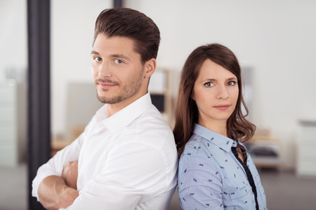 back up: Close up Confident Young Business Couple in Back to Back Inside the Office, Looking at the Camera. Stock Photo
