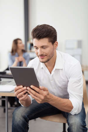 leaning forward: Handsome Young Man Sitting on the Chair with his Body Leaning Forward, Looking at his Tablet Screen Closely on his Hands.