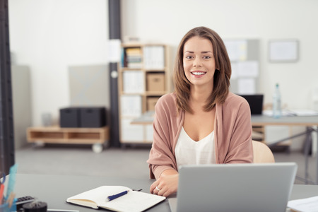 business woman working: Pretty Blond Young Office Woman Sitting at her Desk with Notes and Laptop, Smiling at the Camera