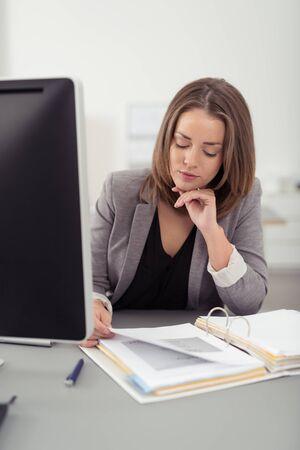 Graves bastante joven Mujer de la oficina Documentos de lectura en su escritorio con una mano en la barbilla