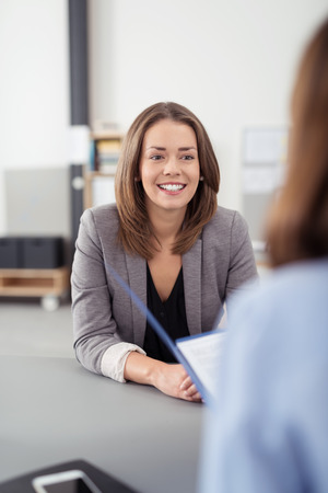 corporate meeting: Pretty Young Professional Job Seeker Woman Being Interviewed by a Manager Inside the Office with a Happy Facial Expression. Stock Photo