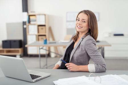 Vrolijke Jonge kantoor vrouw zit op haar bureau met een laptop computer, lachend naar de camera.