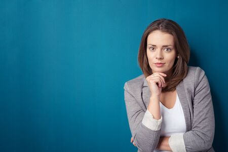 office wall: Half Body Shot of a Confident Young Office Woman with Hand on her Chin, Leaning Against Plain Blue Wall with Copy Space and Looking at the Camera.