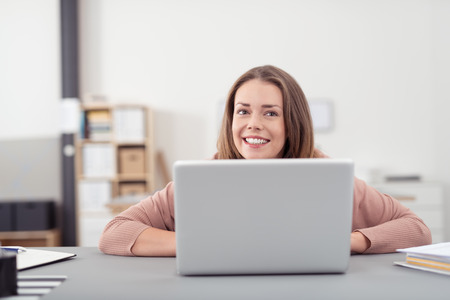 company job: Happy Young Office Woman with Laptop Computer Sitting at the Table and Smiling Into Distance.