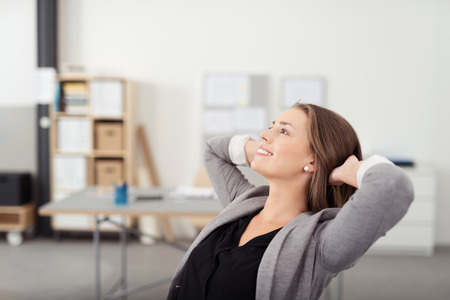 designer chair: Smiling Pretty Woman Leaning her Back on a Chair with Hands her Head While Relaxing in the Office During her Break Time.