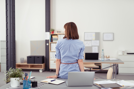 back view: Rear View of an Office Woman Leaning her Back Against the Table with Notes and Laptop, and Looking Into Distant.