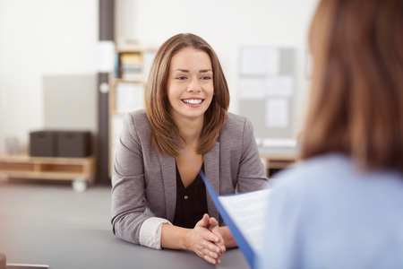 entrevista: Sonriendo bastante joven mujer oficina escuchando a un colega mientras que haciendo una reuni�n en la Mesa.