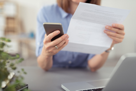 bill payment: Businesswoman making a call on her mobile concerning a paper document she is holding in her hand, close up view Stock Photo
