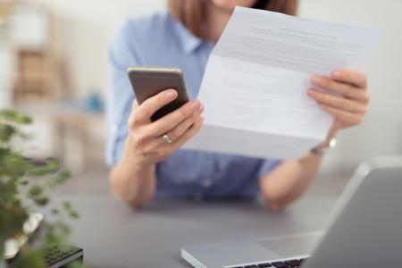 correspondencia: Empresaria que hace una llamada en su móvil en relación con un documento de papel se está celebrando en la mano, vista de cerca