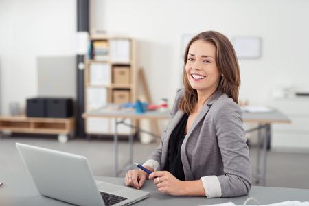 Fröhlich Recht Büro Frau sitzt an ihrem Schreibtisch mit Laptop-Computer, Offenes Lächeln Zeigen an der Kamera. Standard-Bild - 43162988
