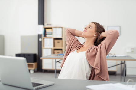 holding head: Thoughtful Young Office Girl Relaxing at her Workplace While Leaning her Back on a Chair and Looking Up with Both Hands Holding Behind her Head