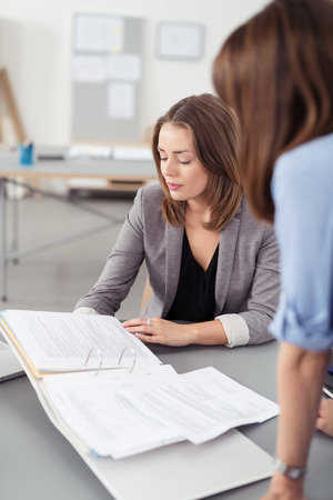 folder with documents: Two Young Office Women at the Table Looking at the Business Documents in Folder. Stock Photo