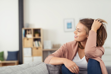 woman young: Thoughtful Young Woman Sitting on a Couch at the Living Room and Holding Back her Hair While Smiling Into the Distance. Stock Photo