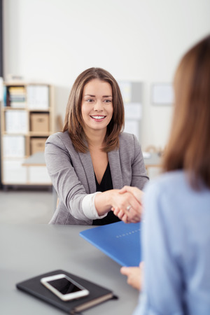 job vacancies: Attractive Young Female Business Agent Shaking Hands with the Client While Sitting at the Table Inside the Office.