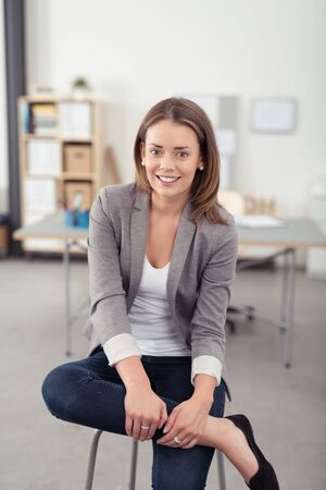 relaxing at home: Pretty Young Professional Woman Sitting on a Stool with Legs Crossed Inside the Office, Smiling at the Camera
