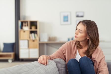 Pensativo mujer joven que se sienta en un sofá en la sala de estar con las rodillas y mirando a la distancia.