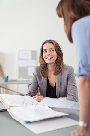 two people talking: Two Professional Women Talking at the Table Inside the Office About the Business Documents in a Folder. Stock Photo