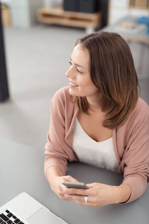 person reading: Close up Happy Thoughtful Office Woman Sitting at her Desk, Holding her Mobile Phone While Looking Into Distance. Stock Photo
