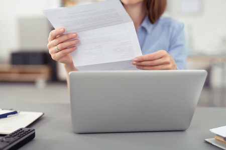 Businesswoman reading a handheld letter or document as she sits at her desk in the office in front of a laptop computer