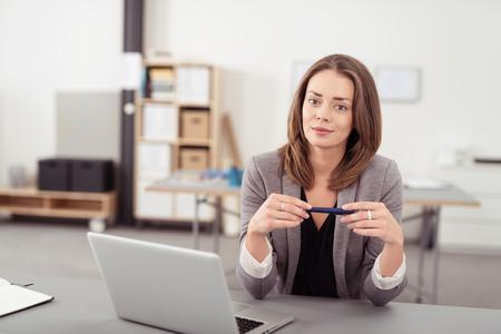 mujer sola: Empresaria joven atractiva Holding Pen, Sentado en el su escritorio con la computadora portátil y mirando a la cámara. Foto de archivo