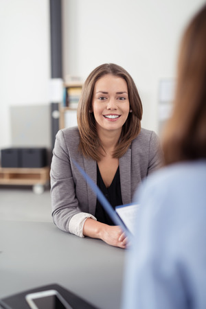 applicant: Attractive Young Businesswoman in an Interview Inside the Office, Smiling at the Camera