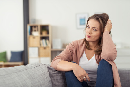 living: Pretty Young Woman Sitting on Couch In the Living Room with Knees Up and Hand on Head, Looking at the Camera.