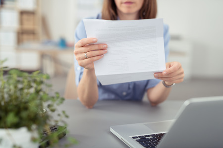 home work: Businesswoman sitting at her desk in front of a laptop computer reading a folded document, close up of her hands and the paperwork