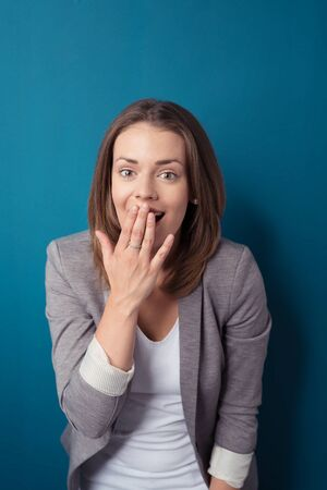 woman surprise: Half Body Shot of a Surprised Young Businesswoman with Hand Over her Mouth, Looking at the Camera Against Blue Green Wall Background.