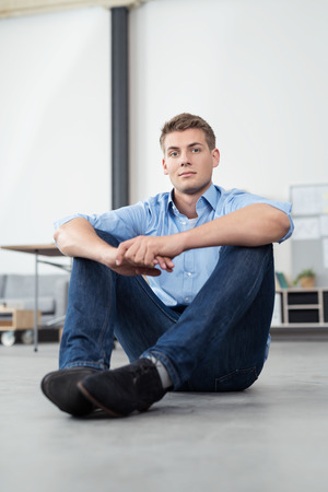 handsome young man: Handsome Young Office Man Sitting on the Floor with Arms Leaning on his Knees and Looking at the Camera