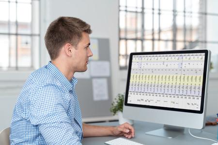 hoja de calculo: Hombre de negocios hermoso joven que se sienta en su mesa dentro de la oficina, buscando en el Informe sobre la pantalla de ordenador. Foto de archivo