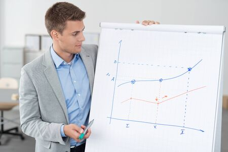 business chart: Handsome Young Businessman Showing his Conceptual Business Graph on a Poster Paper While Holding a Marker Pen.