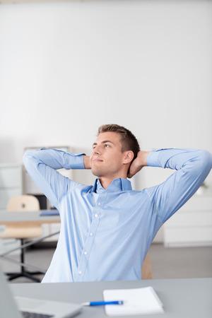 ejecutivo en oficina: Pensativo Hombre de negocios hermoso joven que se relaja en su silla con las manos que sostienen la parte posterior de su cabeza y sonriendo en la distancia. Foto de archivo