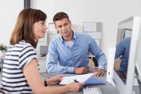 secretarias: Dos trabajadores de oficina sentado en la mesa dentro de la oficina y mirando a la pantalla del ordenador Juntos para Verificar alguna información.