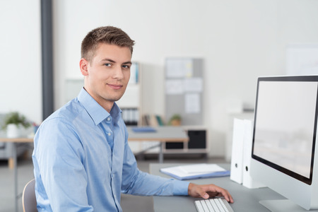 blank screen: Half Body Shot of a Smiling Good Looking Young Businessman Sitting at his Desk Inside the Office, Smiling at the Camera. Stock Photo