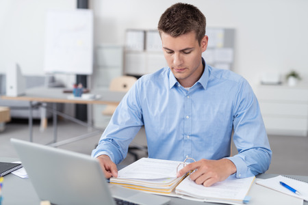 reviewing: Handsome Young Businessman Sitting at his Desk Inside the Office, Reading Some Documents on a Binder Seriously Stock Photo