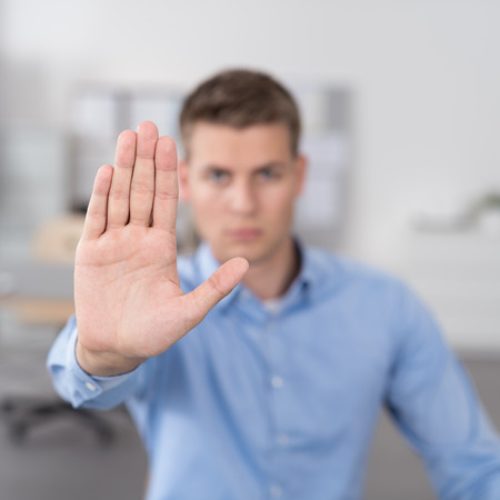 stop: Young Businessman Showing Conceptual Stop Hand Sign in Close Up at the Camera. Stock Photo