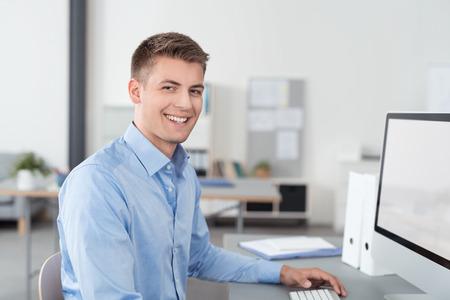Half lichaam shot van een gelukkig knappe jonge zakenman zit aan zijn bureau met computer in het bureau.