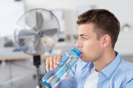 Close up Handsome Young Man Inside the Office, Drinking a Bottle Water While Looking Into Distance. Stock Photo