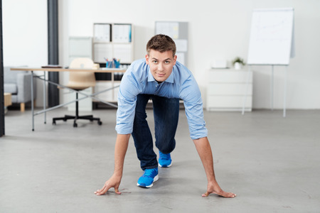 start business: Front View of a Handsome Young Office Man in a Race Starting Position on the Floor, Looking at the Camera