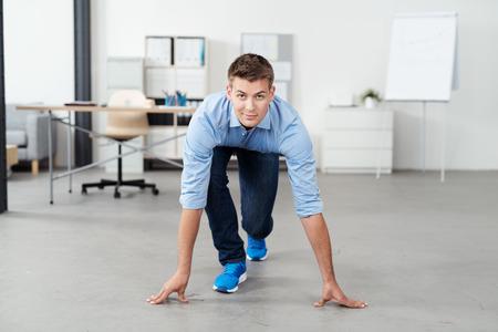 Vooraanzicht van een knappe jonge Office Man in een race beginnen standpunt over de vloer, kijken naar de camera