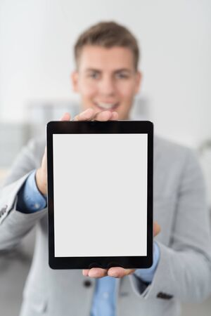 emphasizing: Young Businessman Showing an Empty White Tablet Computer Screen in Close up, Emphasizing Copy Space.