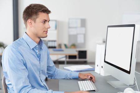 Knappe jonge zakenman zit aan zijn bureau binnen het kantoor, staren naar het computerscherm tijdens het lezen sommige rapporten