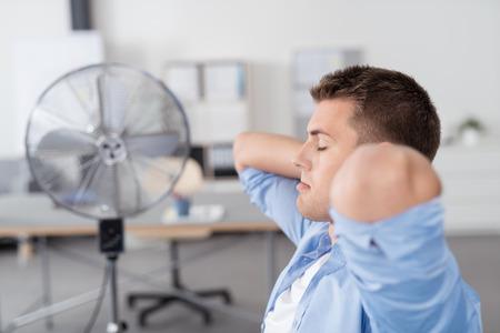 sudando: Cansado hombre de negocios joven que se relaja en su silla con ambas manos con la cabeza y los ojos cerrados dentro de la oficina.