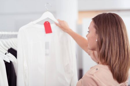 sale tag: Close up Young Woman Looking at Plain White Shirt on a Hanger with Red Tag Inside the Clothing Store Stock Photo