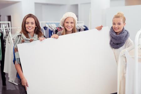 winter fashion: Three Young Women in Winter Outfits, Holding Large White Poster with Copy Space Inside the Clothing Store and Smiling at the Camera. Stock Photo