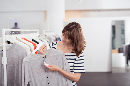 Young Woman Looking at the Price Tag of a New Casual Gray Shirt on a Hanger Inside a Department Store.