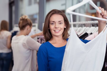 garments: Smiling young woman shopping for fashion garments in a boutique store holding up a filmy white summer top with a smile Stock Photo
