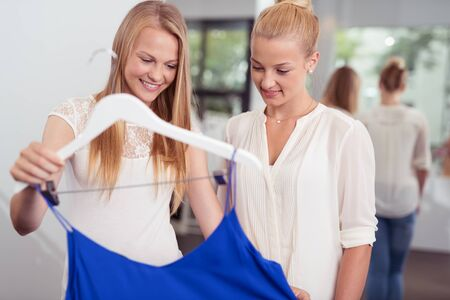 conscious: Two young fashion conscious women standing discussing a blue top on a fashion boutique or clothing store smiling as they examine the fabric